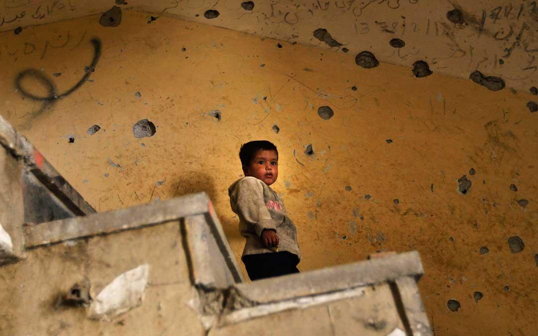 2010年10月21日,阿富汗喀布爾,一名阿富汗男孩站在充滿彈孔的牆前。攝:Chris Hondros/Getty