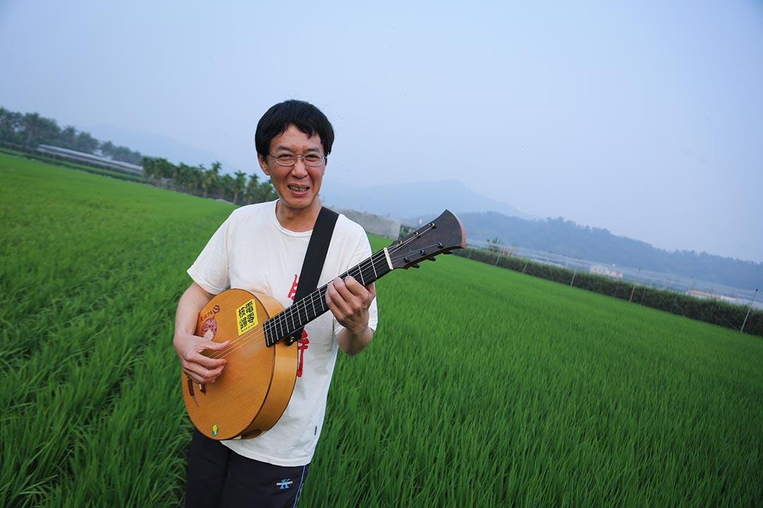 林生祥在高雄美濃家附近的田野演奏樂器。攝:徐翌全/端傳媒