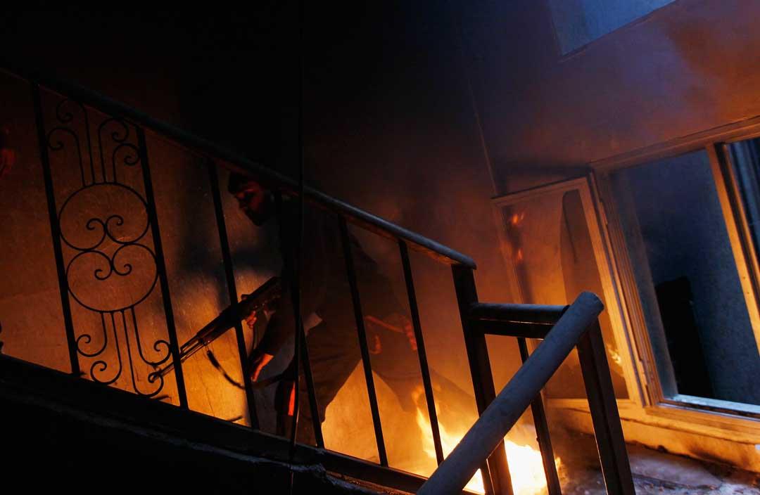 2011年4月20日,利比亞,反政府軍進入大樓作戰,反政府軍走上樓梯,把燃燒的輪胎推向敵人士兵的房間。攝:Chris Hondros/Getty