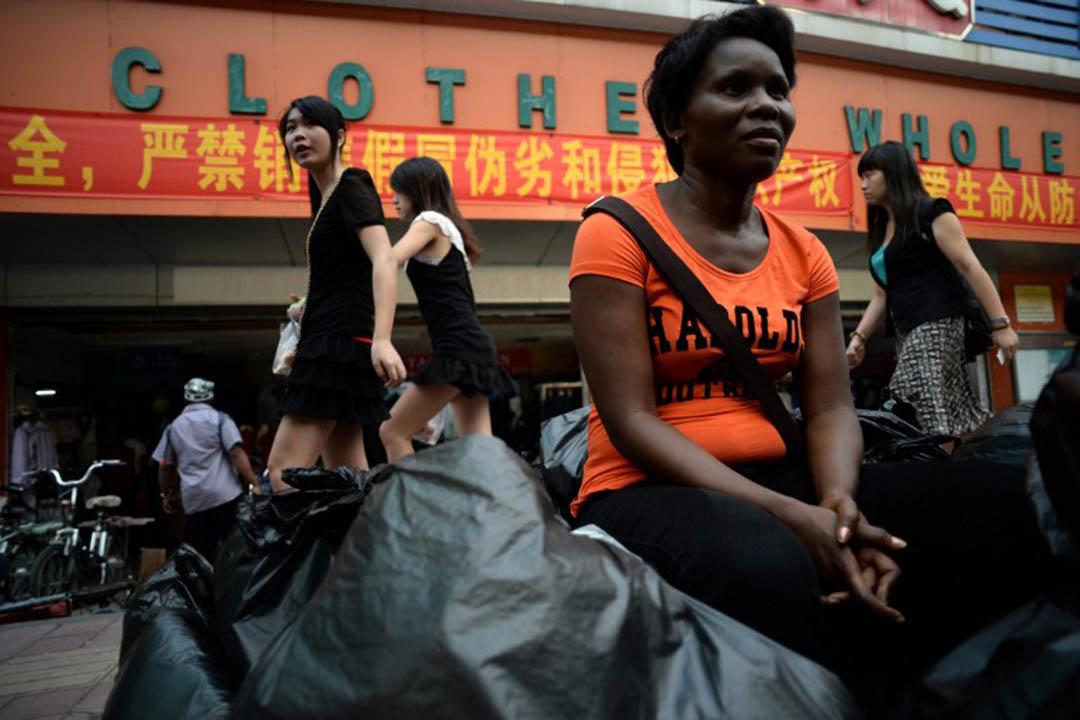 圖為廣州,一名贊比亞商人坐在一個服裝批發市場外。