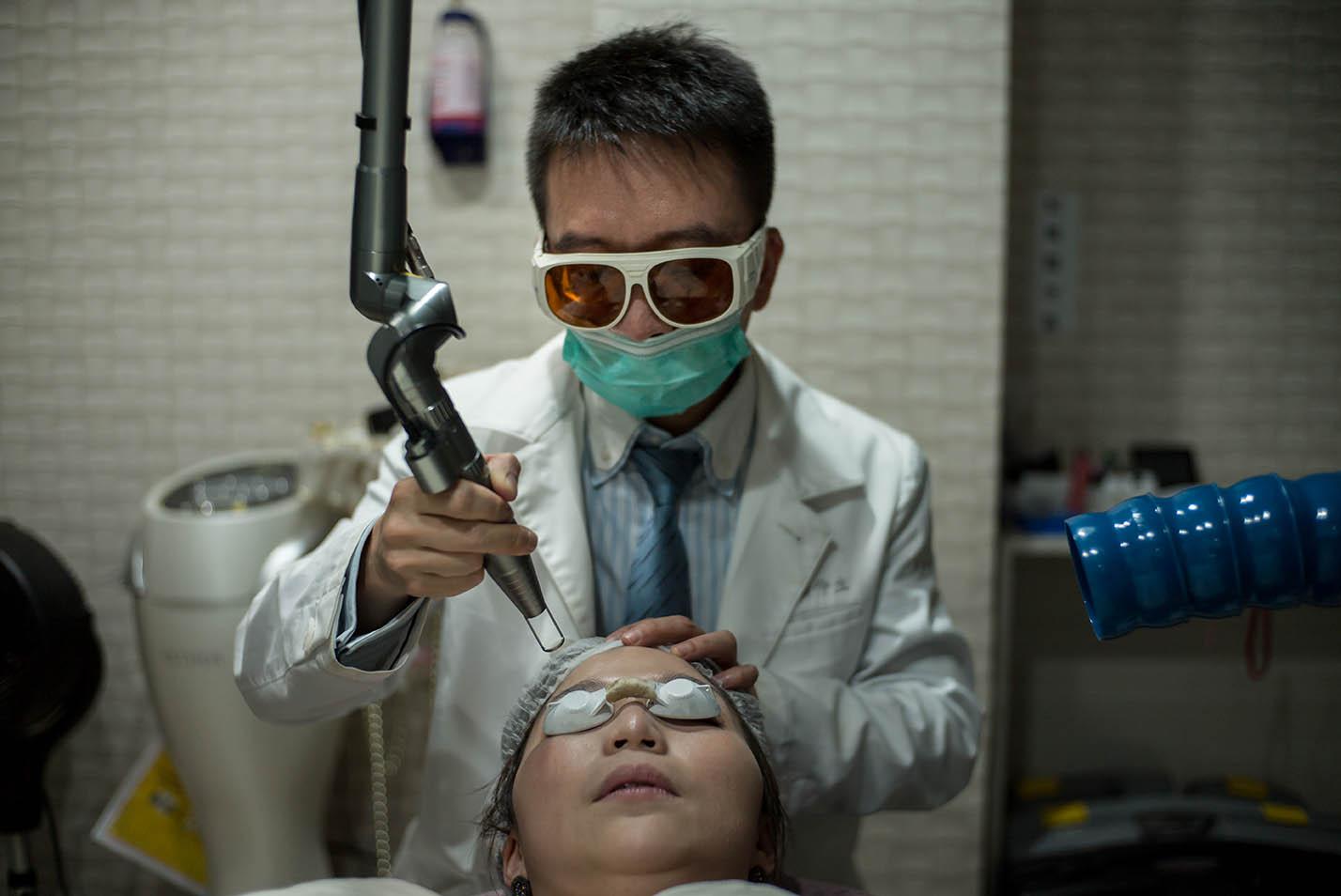 一位美容醫師正在執行雷射手術。攝:Billy H.C.Kwok/端傳媒