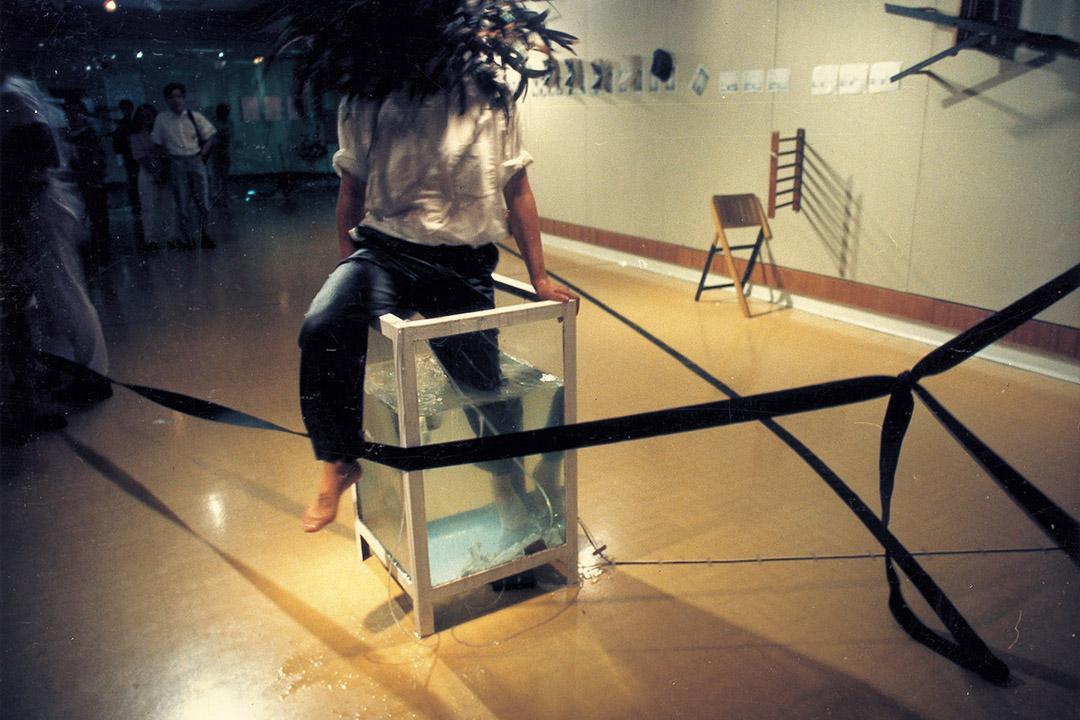 89年7月上環文娛中心多媒介展演《東西遊戲》,鄭志銳的即興形體動作和  蔡仞姿的水缸裝置。