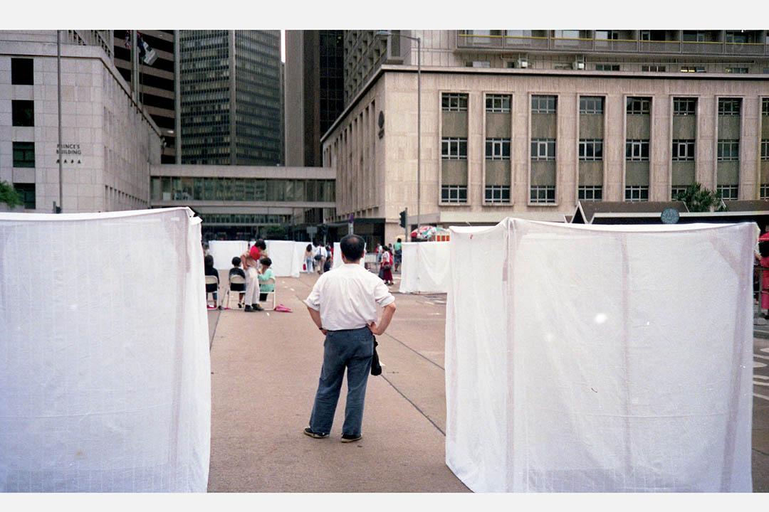 進念「現在進行式:運動(一)」的藝術指導榮念曾,企圖用蚊帳陣法作為「  中國文化深層結構」的基本單位,可那刻出現在遮打道已滿載另外的指涉。