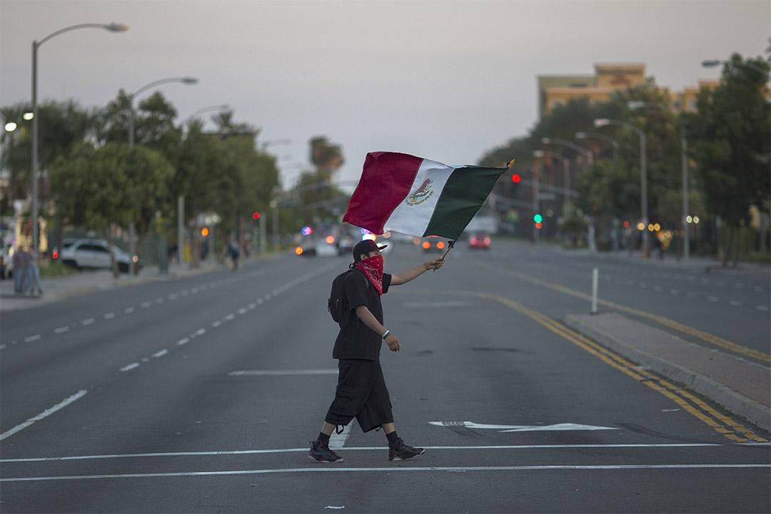 2016年5月25日,加利福尼亞州安納海姆,特朗普競選活動後,一個男士手持墨西哥國旗抗議。