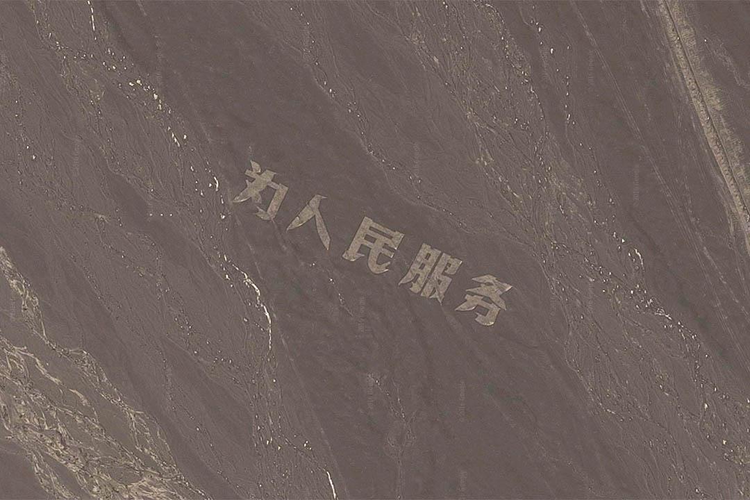新疆哈密戈壁灘用碎石堆積成的巨大「為人民服務」大字。