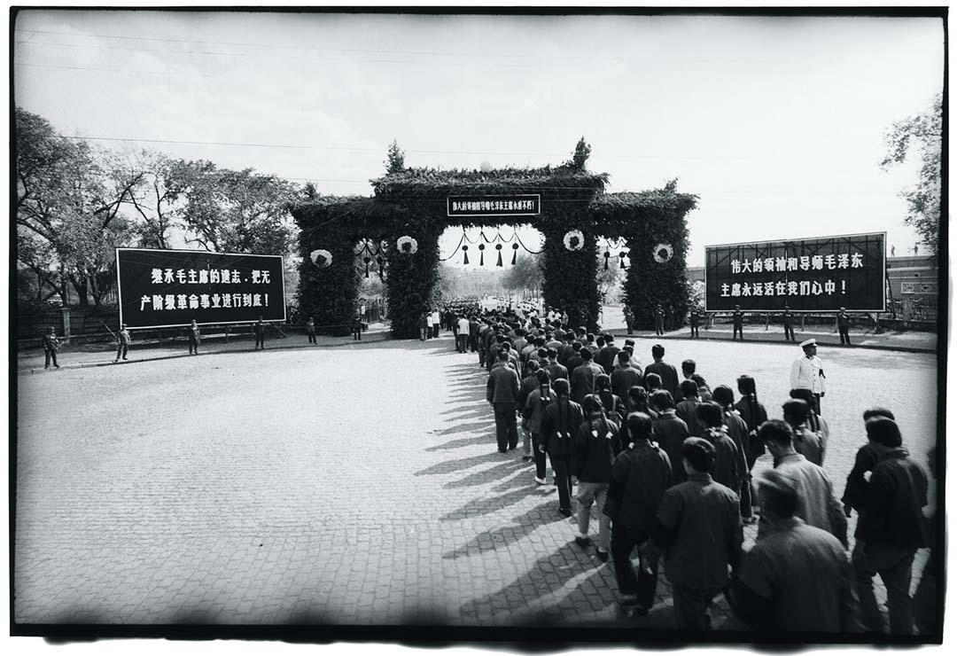 1976年9月18日,哈爾濱,人民前往廣場參加當地悼念毛澤東的儀式。廣場大門前的告示版上寫有:「繼承毛主席的遺志,把無產階級革命事業進行到底!」以及「偉大的領袖和導師毛澤東主席永遠活在我們心中!」。