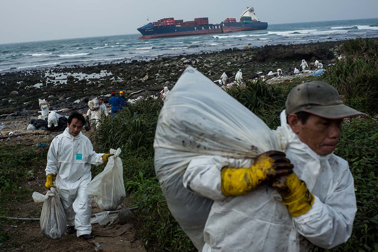 德翔台北漏油事件,造成約1000噸的油流入石門海岸,當地居民忙著清理一袋袋油污垃圾。攝:Billy H.C. Kwok/Getty Images