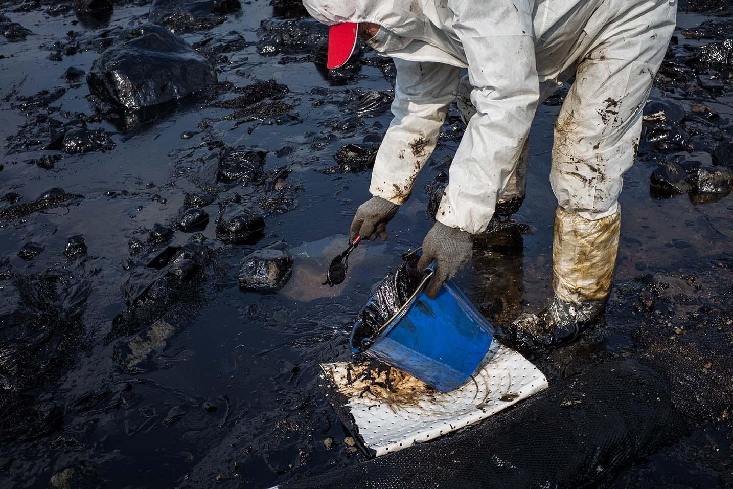 居民用瓢羹撈起沿岸的石油。攝:Billy H.C. Kwok/Getty Images