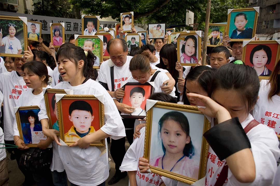 六一兒童節中,汶川大地震中罹難學生的家長手持子女遺照。