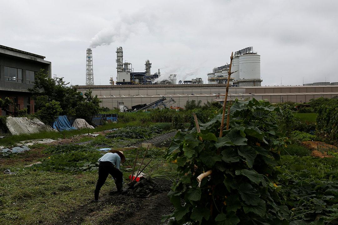 台灣宜蘭一個工業區,一名農民在水泥廠前耕種。