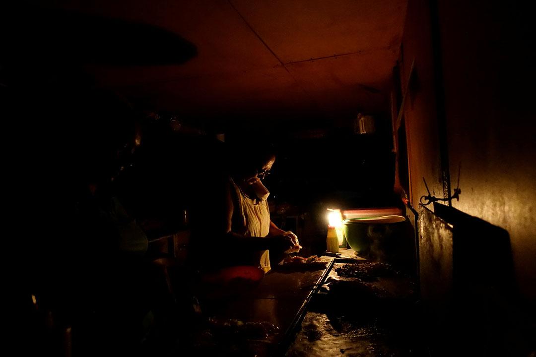 委內瑞拉科赫德斯,一名婦人在燭光下做飯。