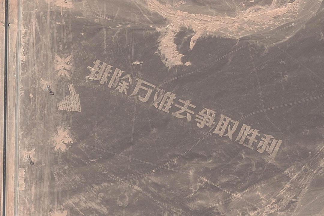 新疆哈密戈壁灘用碎石堆積成的巨大「排除萬難去爭取勝利」大字。