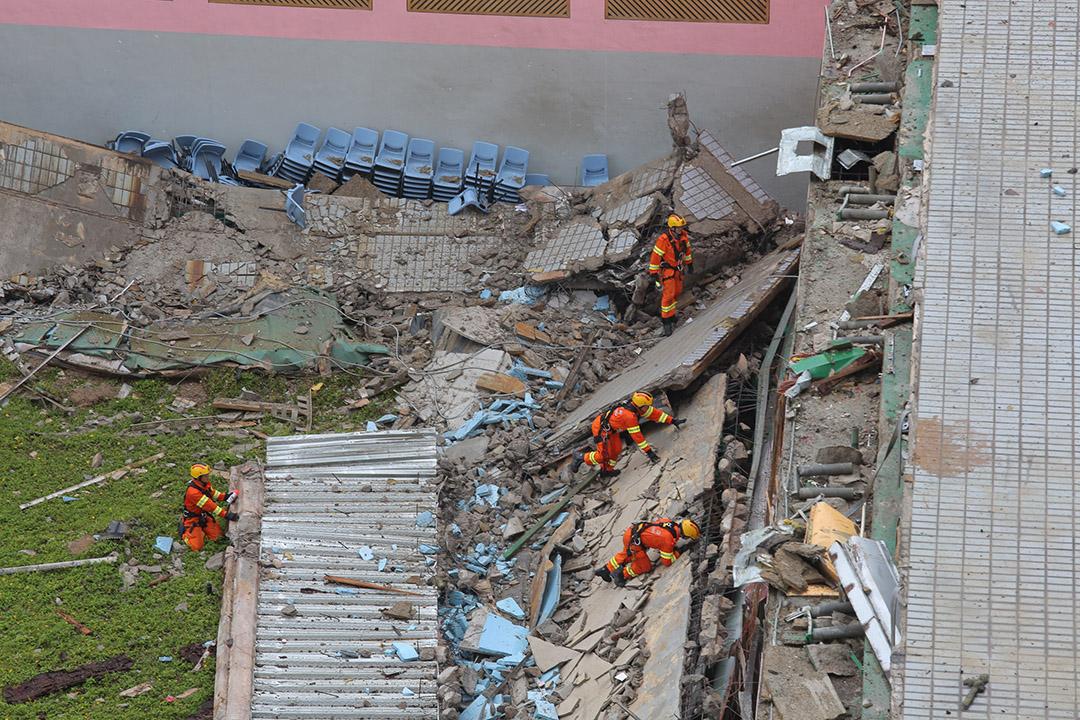 消防員在倒塌樓層搜索。