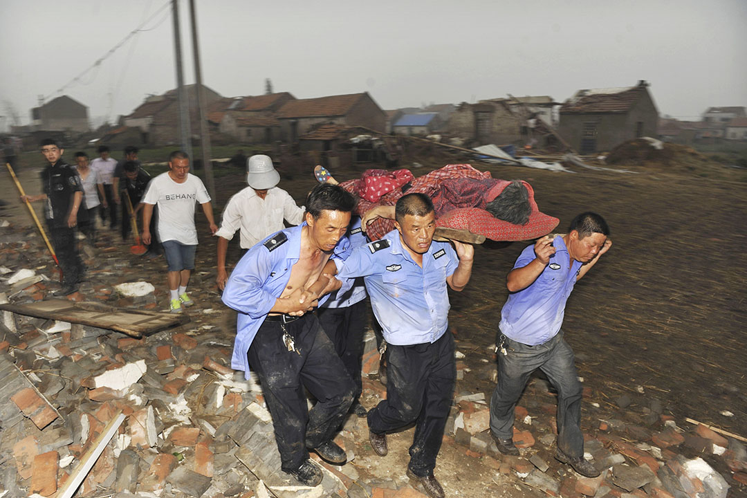2016年6月23日,江蘇鹽城部分地區遭遇強龍捲風,導致公路、建築等大量損毀。圖為救援人員從倒塌的房屋救出一名傷者。