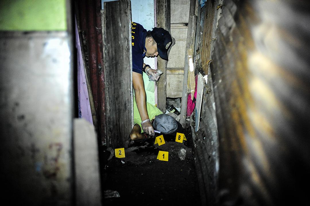 2016年6月25日,菲律賓馬尼拉,三名毒販被槍殺後,法醫檢查其中一具屍體。
