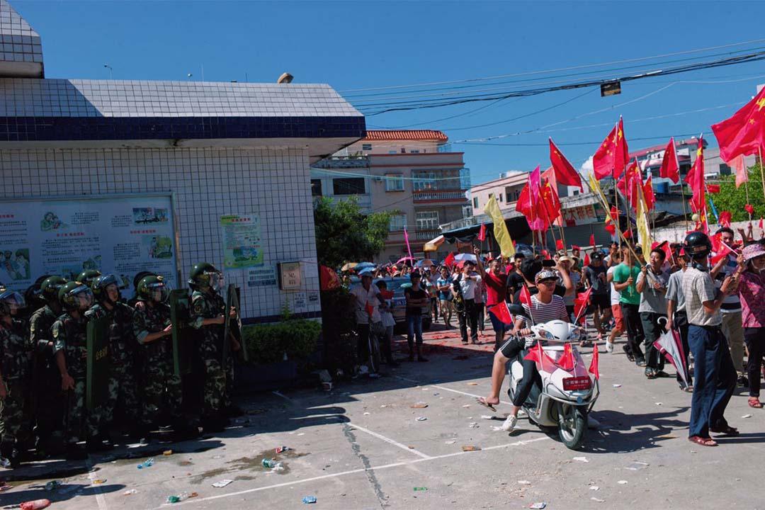 村民於村內遊行,近村口處有百多名公安戒備,部份配備盾牌。