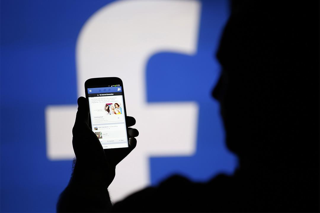 圖為一個人在臉書標誌前使用智能手機。
