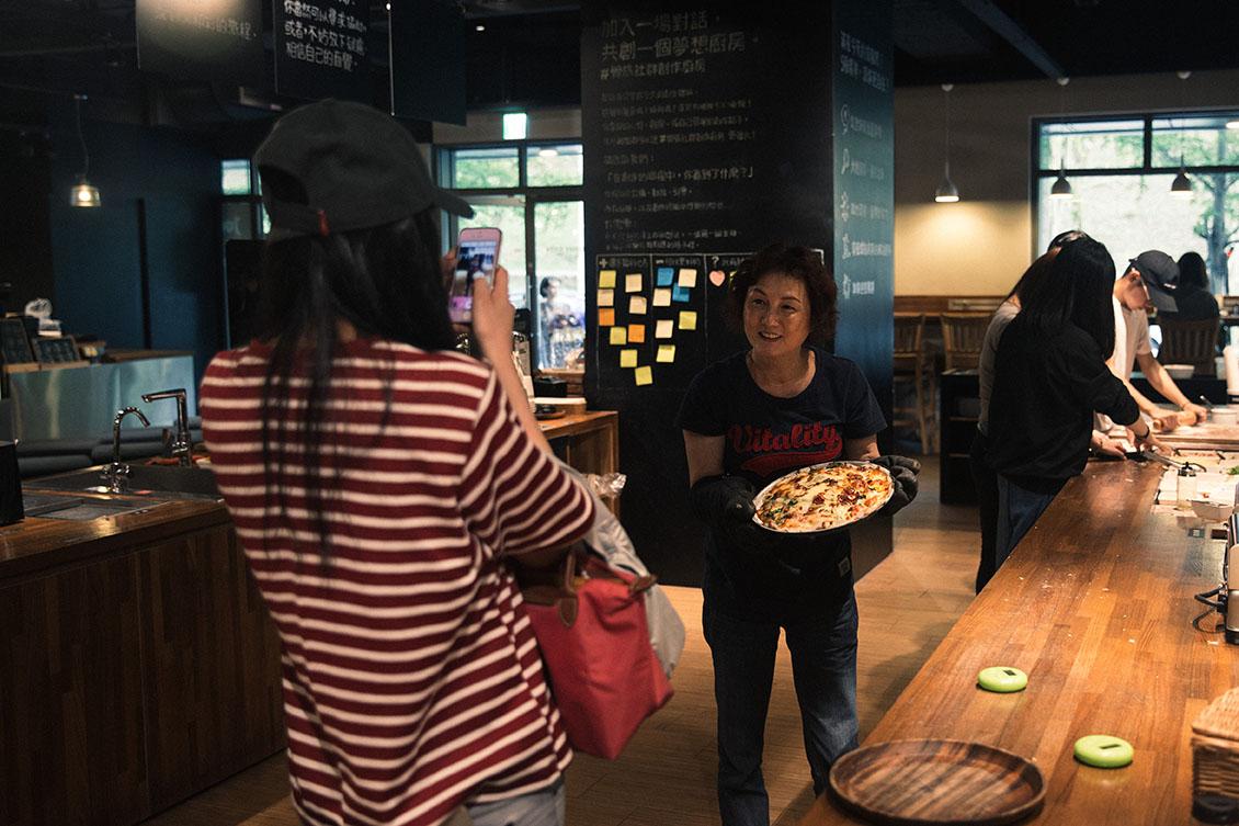 顧客開心地與自己製作的pizza合照。