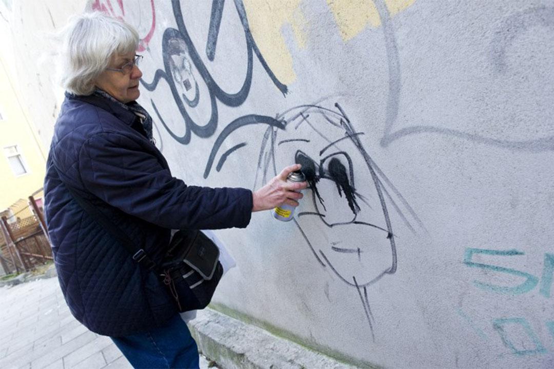 2011年12月20日,柏林利希滕貝格區,66歲的反納粹主義行動者 Irmela Mensah-Schramm 在一個納粹標誌上塗鴉,將標誌覆蓋。
