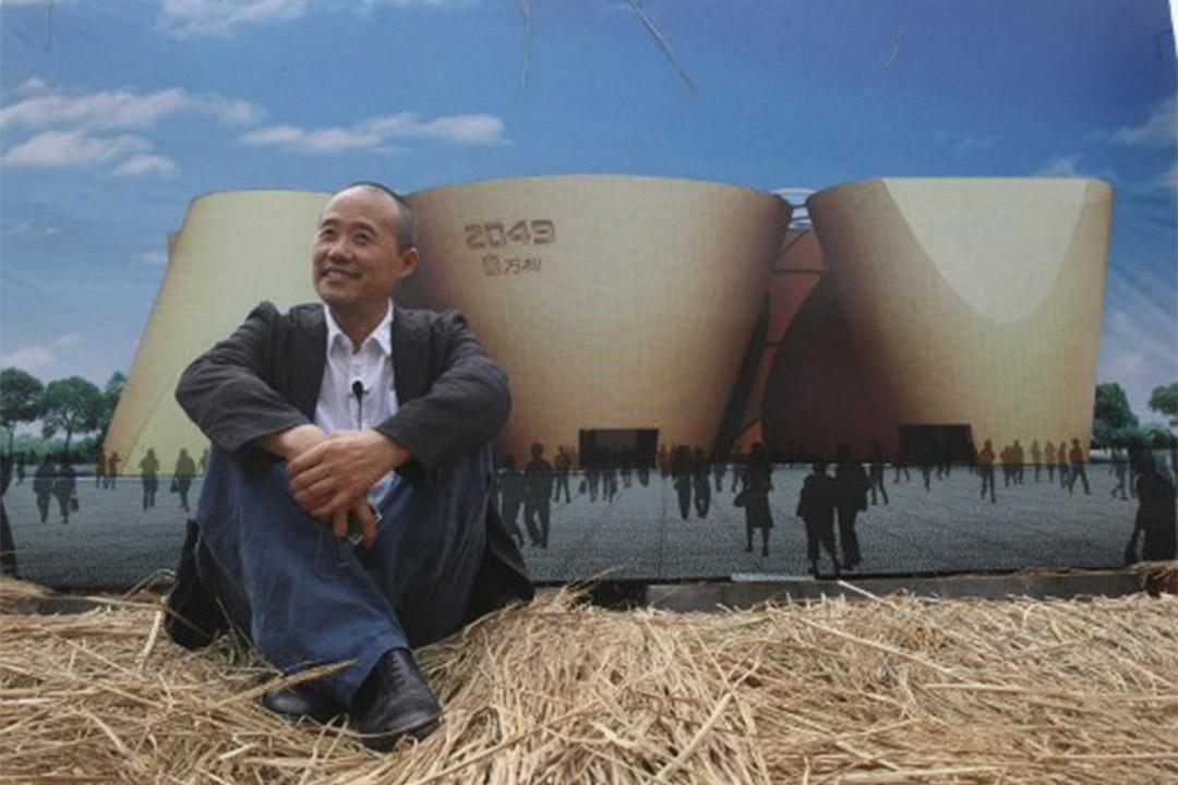 2009年7月29日,萬科集團董事長王石坐在廣告板前讓攝影師拍照。