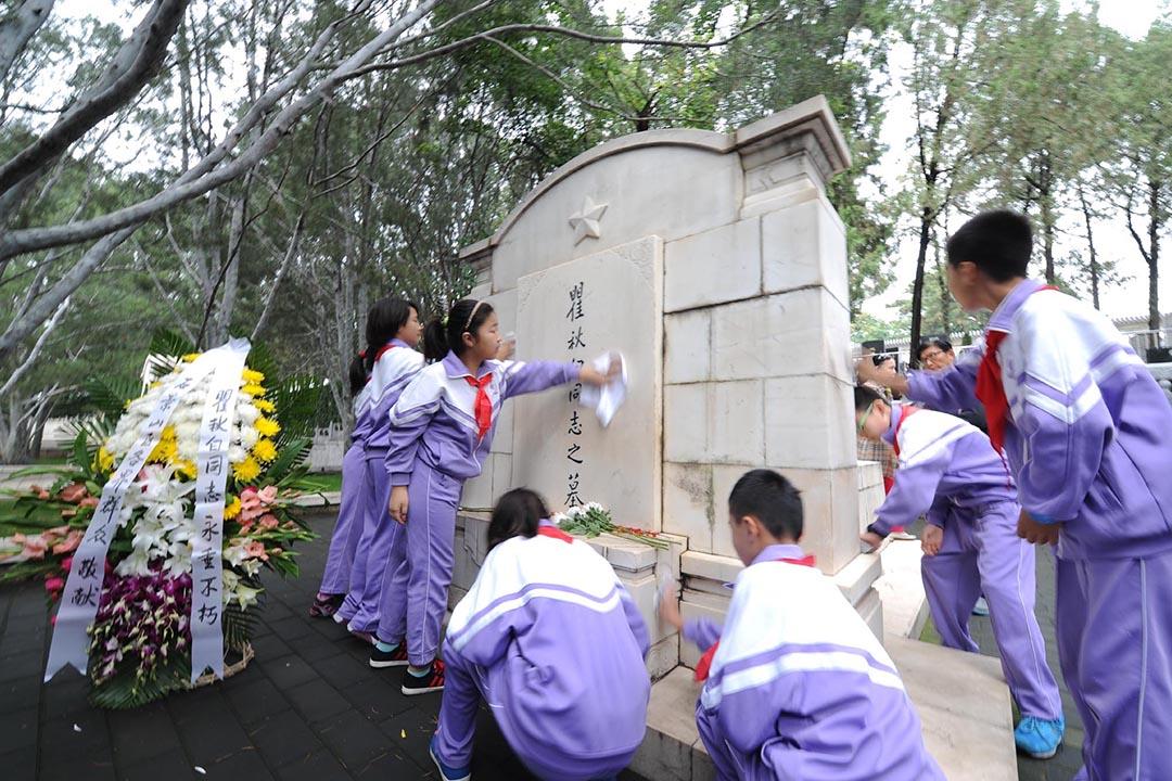北京八寶山革命公墓,學生打掃瞿秋白的墓碑。