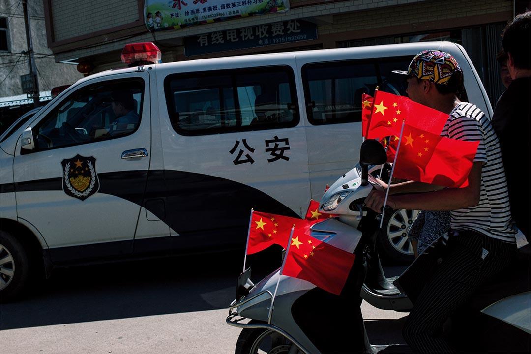 參與遊行的村民乘著插滿國旗的摩托車,駛經停泊於村口的公安車輛。