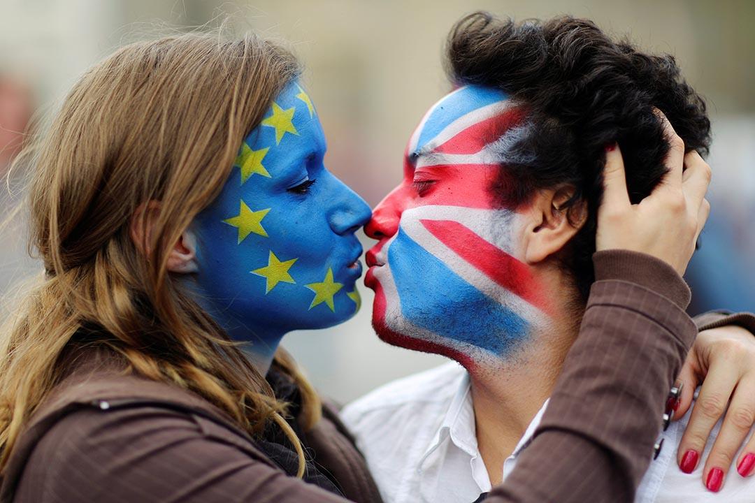 一雙男女臉上畫有歐盟國旗和英國國旗互相親吻對方。