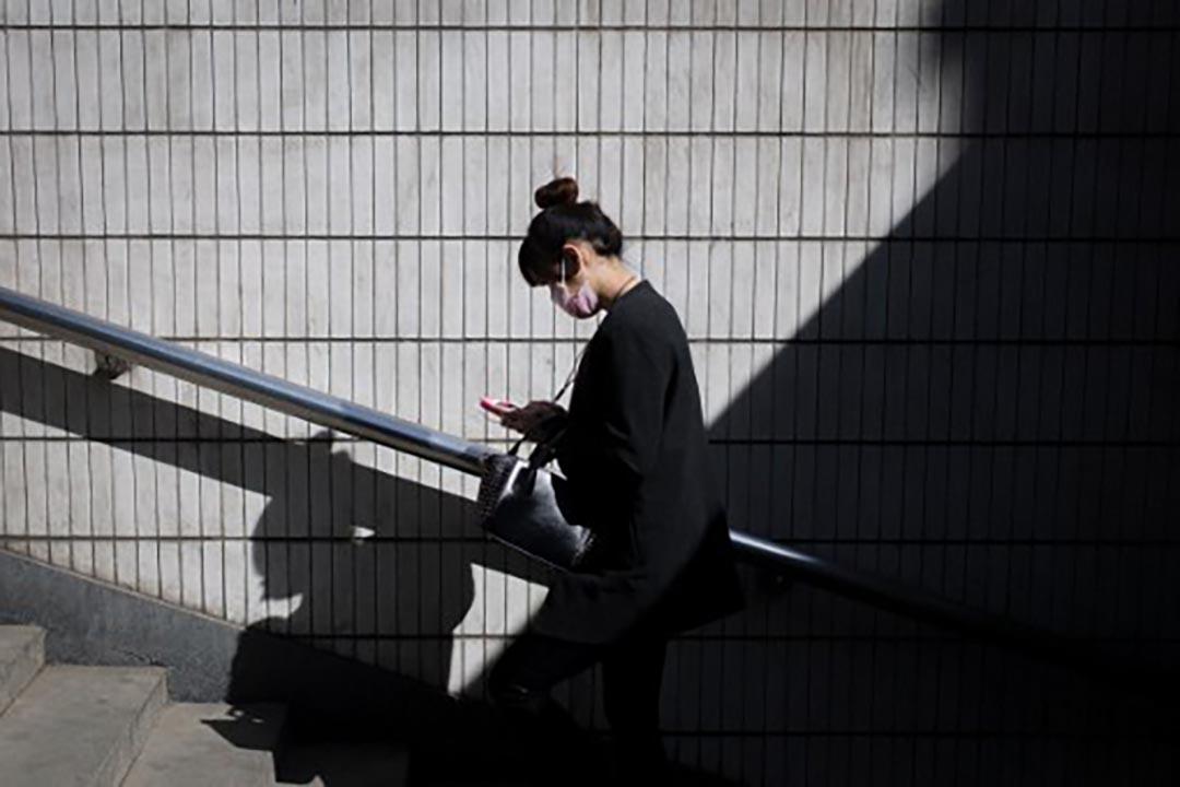一名市民在北京街上看電話。