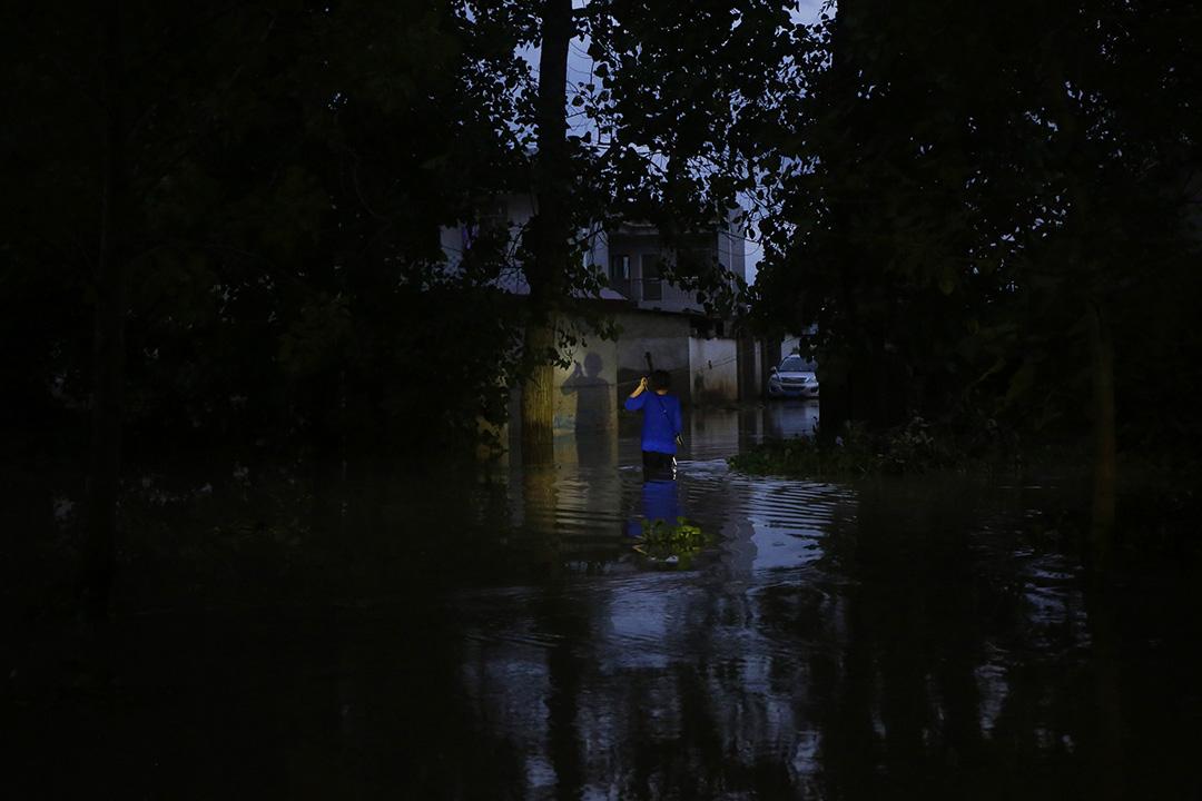 中國武漢,河水缺堤,一名村民在洪水中走路。
