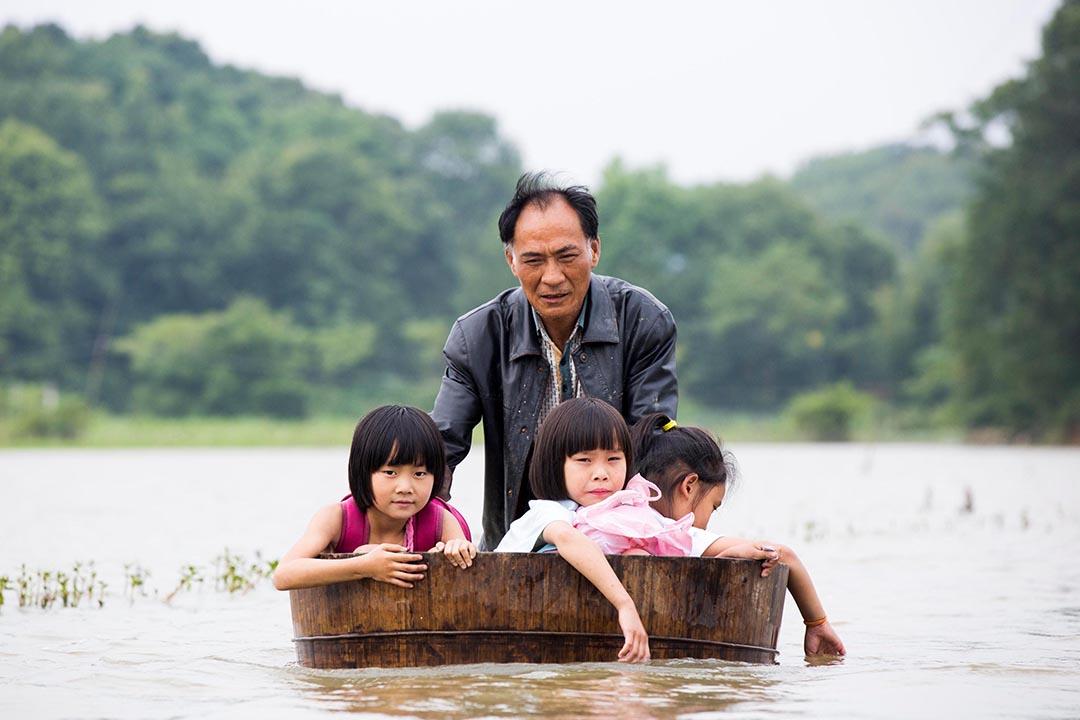 江西省都昌縣,一個男子用木桶載著孩子上學。