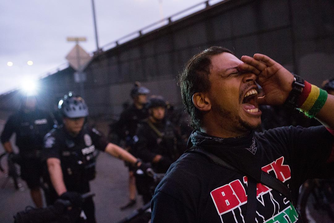 一名示威者在西雅圖示威現場,在警察前面叫喊。