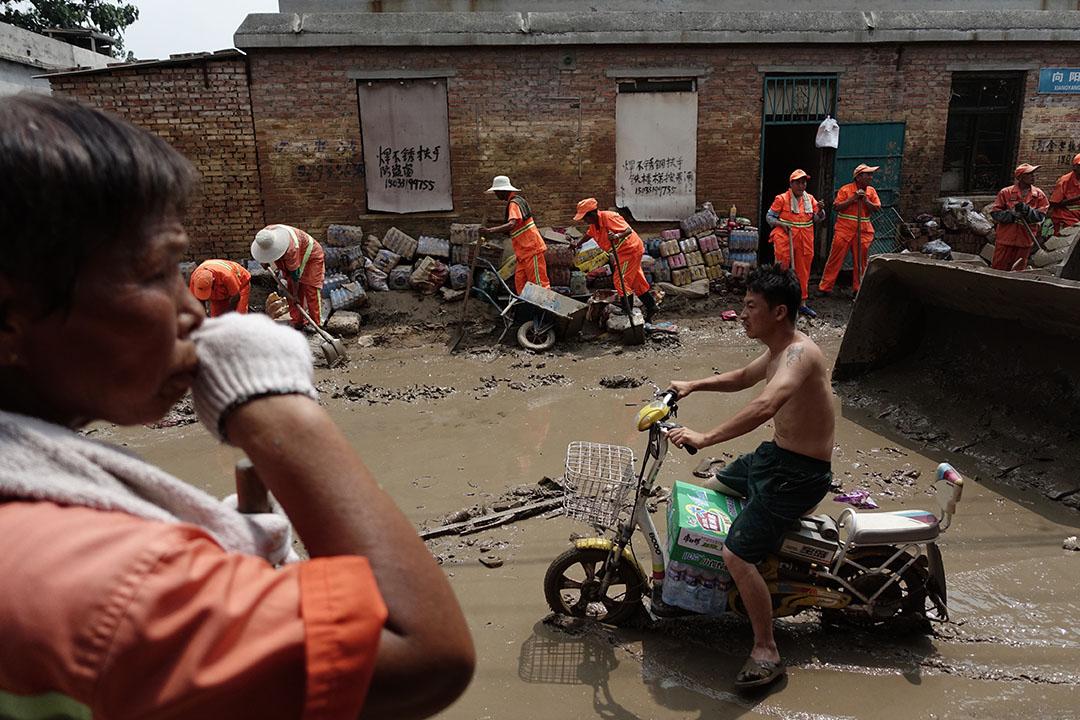 河北邢台大賢村洪災過後,居民和清潔人員打掃街道。