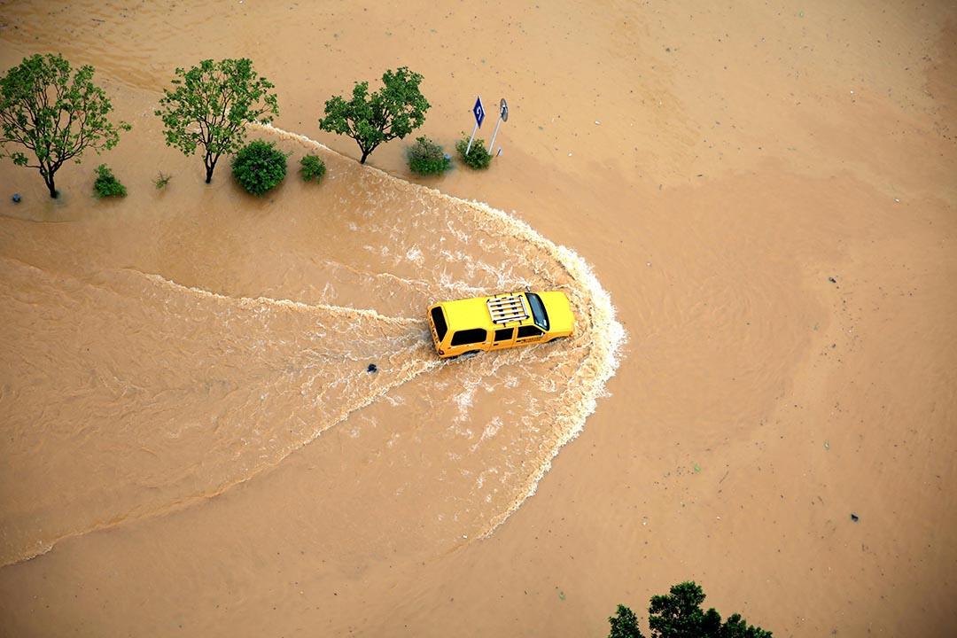 貴州省,一輪汽車在淹水的道路前進。