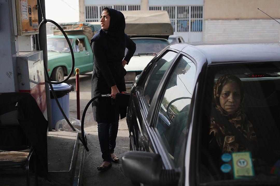 一名伊朗婦人在油站為車子加油。