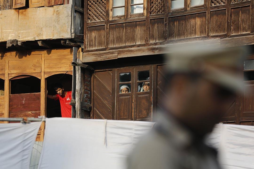 幾名喀什米爾市民看著警察祈禱。