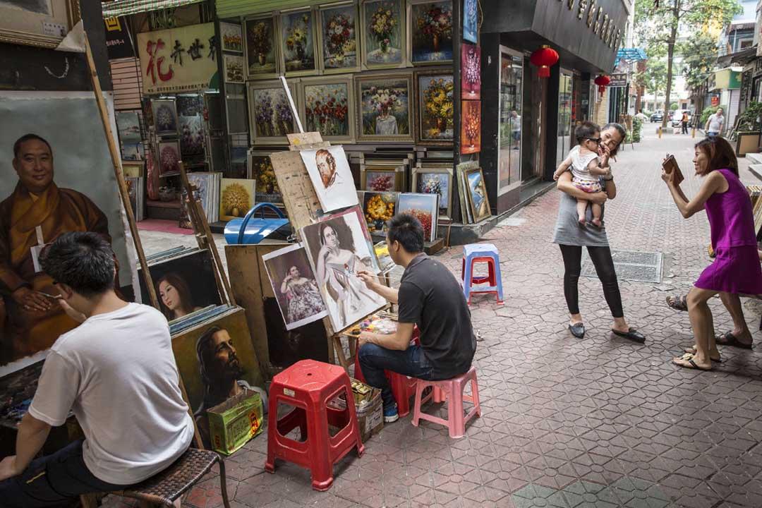 2014年6月12日,深圳大芬村,兩個畫家正在畫攤作畫。