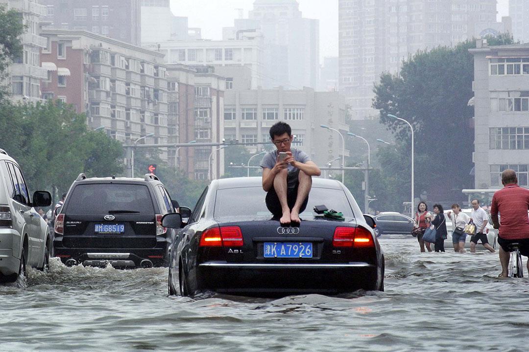 2016年7月20日,中國天津,在被水淹沒的街道上一名男子坐在汽車的頂部。