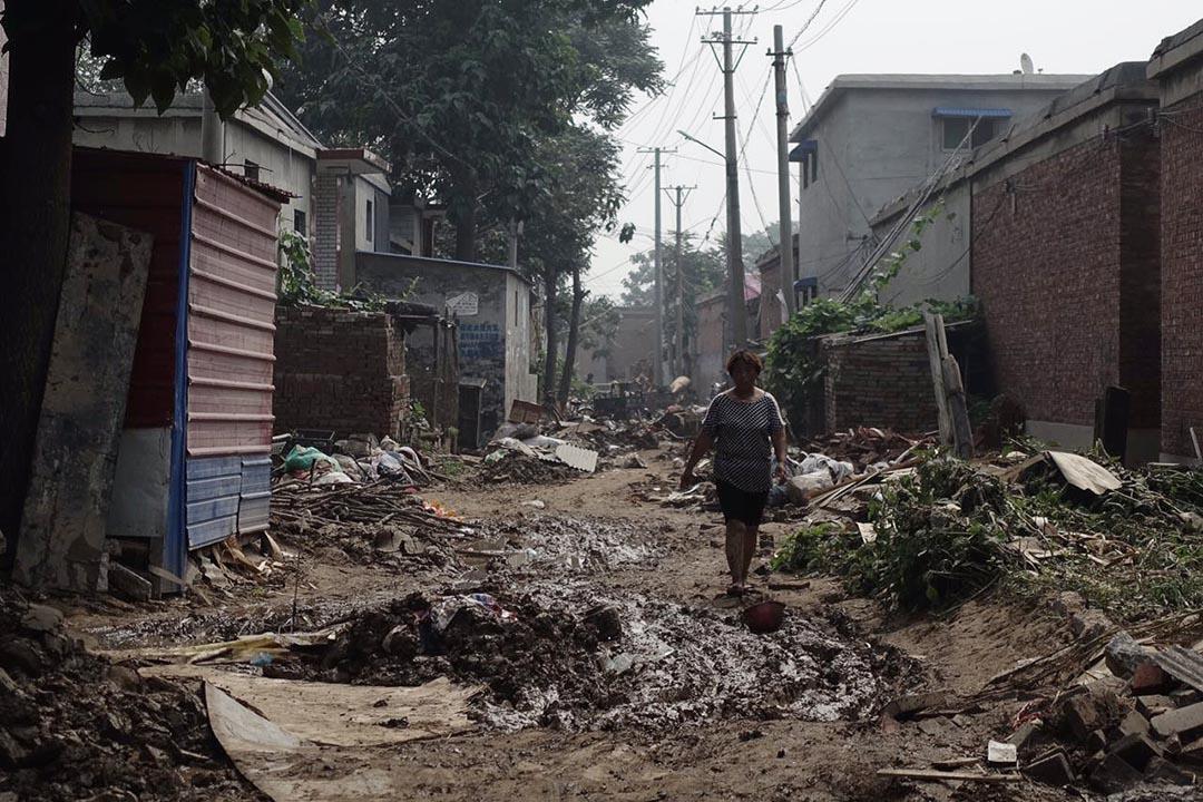 河北邢台大賢村洪災過後,居民街道上行走。