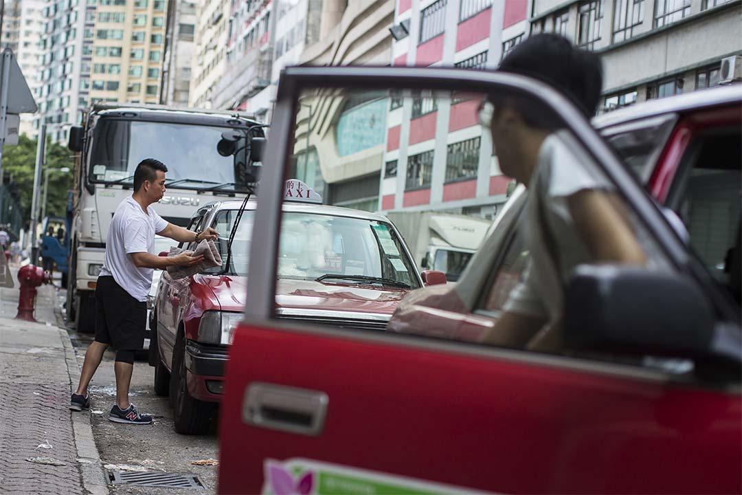 圖為的士司機在休息時間洗刷車身。