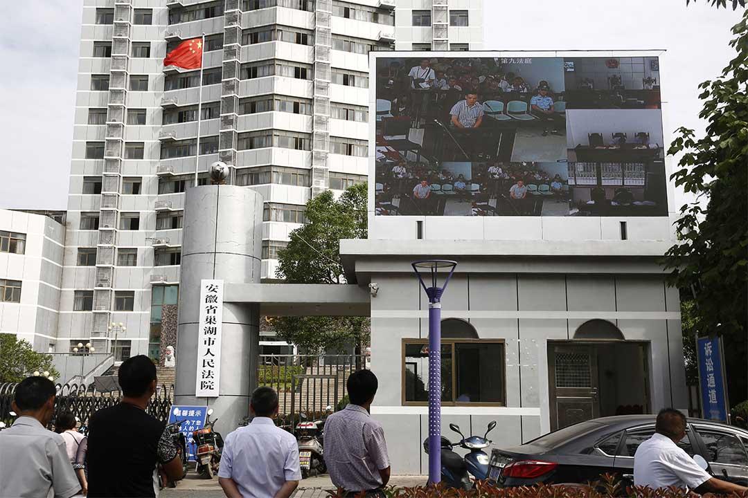 圖為2015年9月10日,安徽省巢湖市法院外,一個顯示屏正在直播審訊。