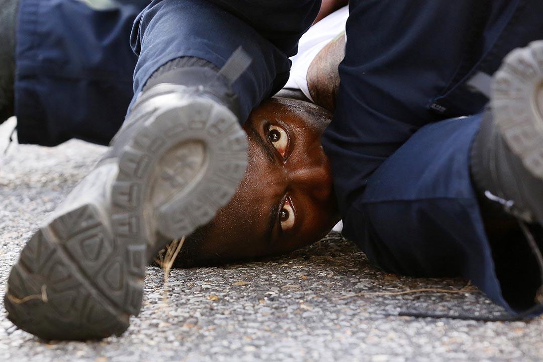 一名示威者被警察制服在地上。