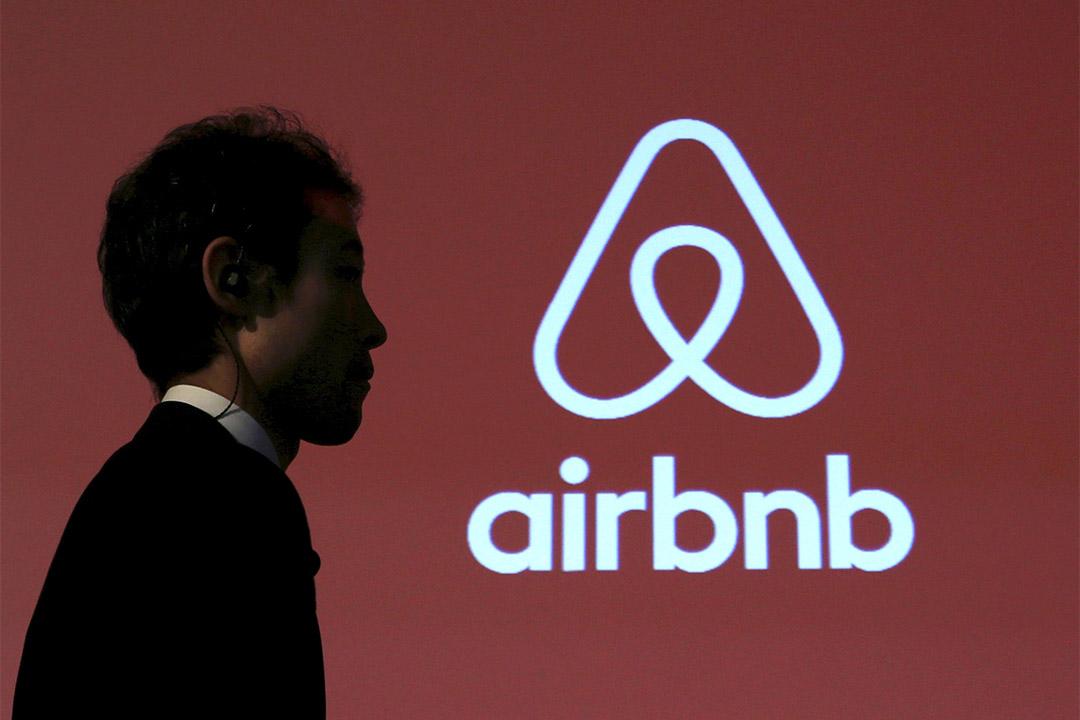 圖為一個男士走過Airbnb的標誌。