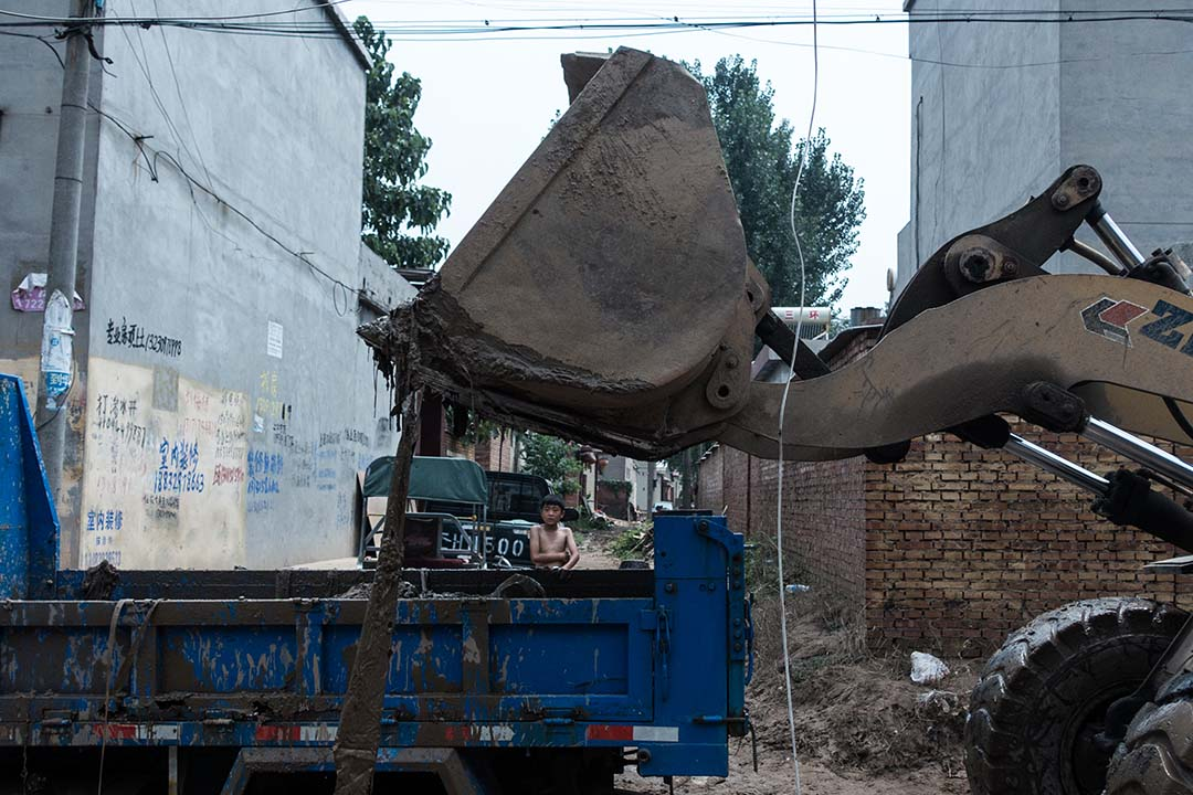 大賢村的村民清理淤泥,希冀淤泥裏還有一些現金和未被損壞的貨物。