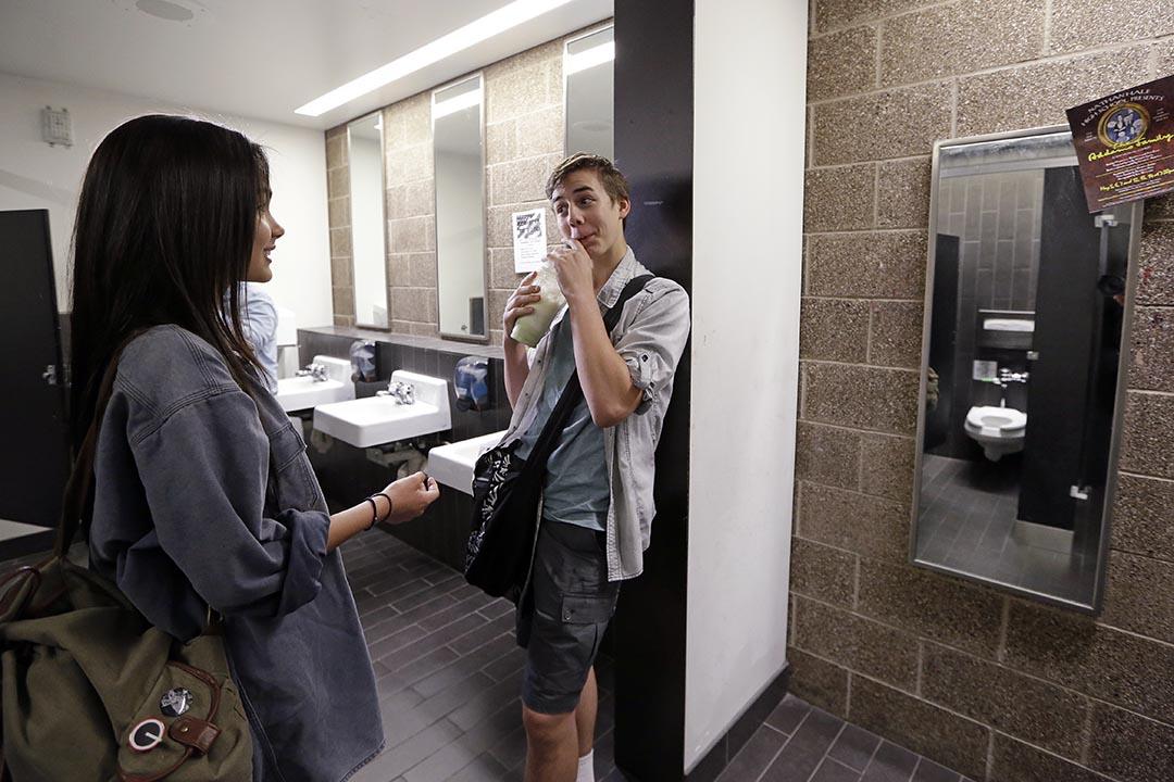 九年級學生Tehya Vining(左)和 Christian Jarboe首次Nathan Hale 中學的性別中立廁所內交談。