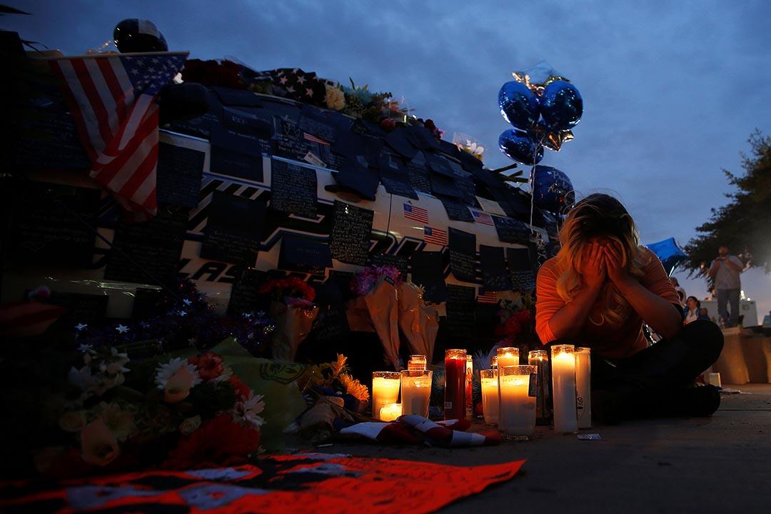 一名市民悼念不幸在槍擊案身亡的五名警察。