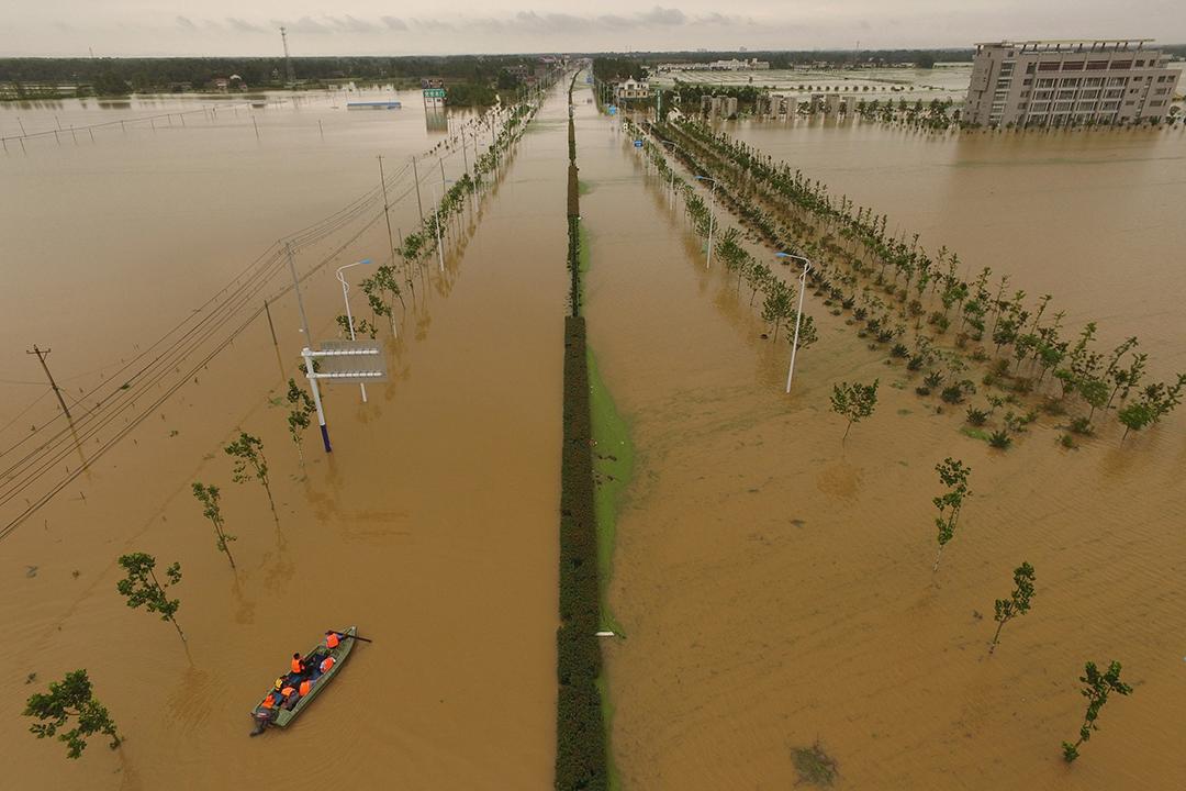 中國安徽,救援人員乘船檢查被洪水淹沒的道路。