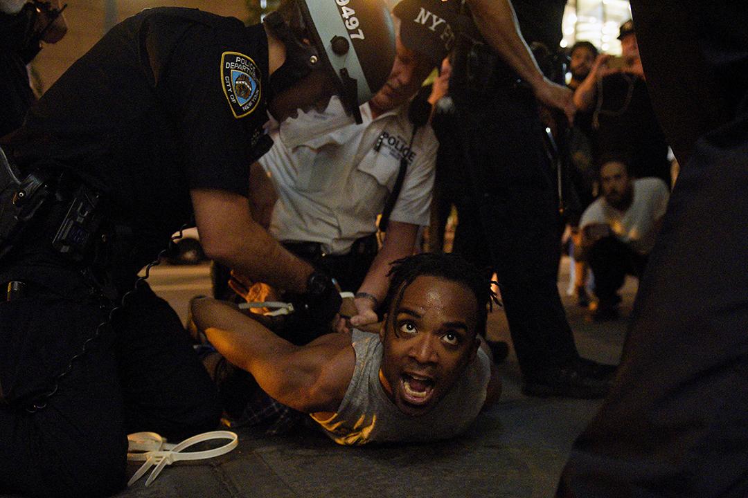 紐約示威中,一名黑人被警察按壓在地上拘捕。