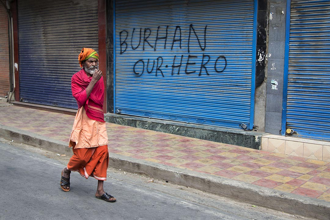 一名僧侶走過一家門外噴有支持Burhan Wani口號的店鋪。