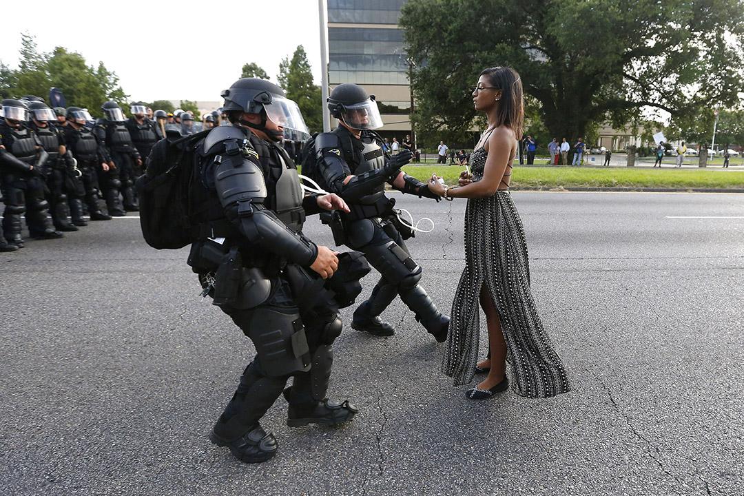 路易斯安那州的示威中,一個黑人女人兩手空空,站在衝向她的防暴警察面前。