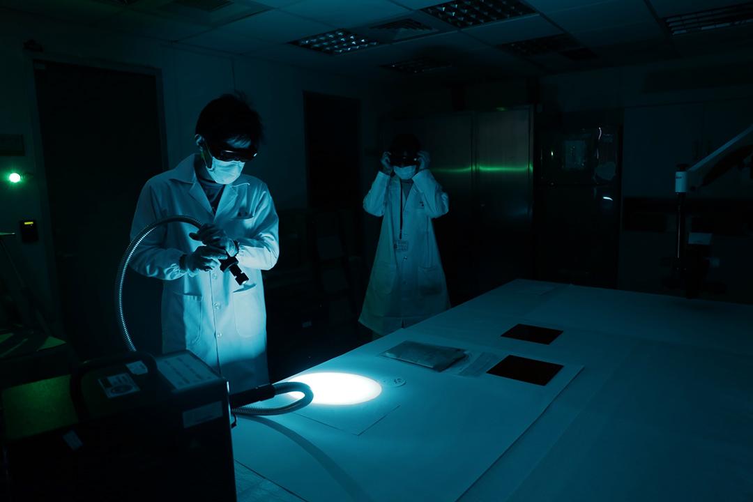 鑑識人員用紫外光燈檢視證物。